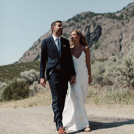 Newlyweds walking down gravel road with mountains in background.