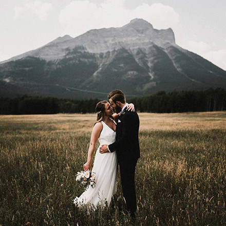 Newlywed portrait in front of a mountain with groom wearing an INDOCHINO suit.