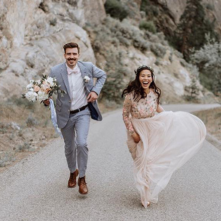 Newlyweds running down road with the groom wearing an INDOCHINO suit.
