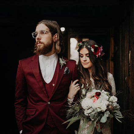 Portrait of a bride and groom, with groom wearing a burgundy INDOCHINO suit.