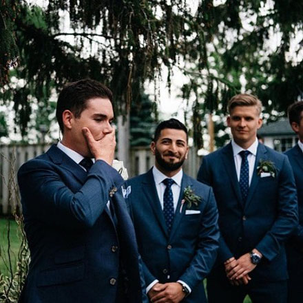 A groom holding his emotions while his groomsmen watch.