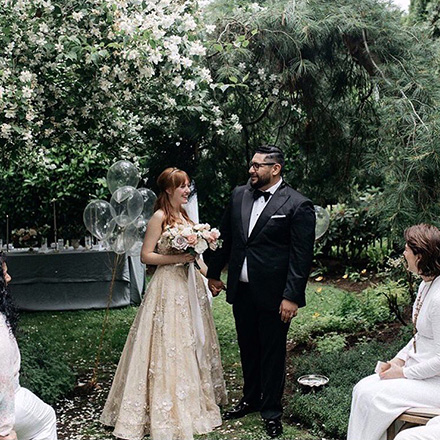 Newlywed couple in a lush garden.