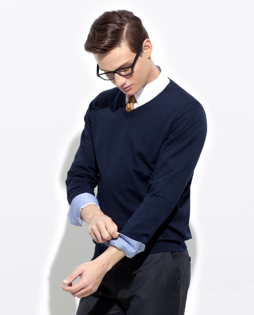 A man modeling a navy sweater and charcoal pants.