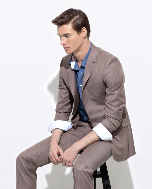 A model wearing a medium sand colored pin-stripe suit with a blue shirt.