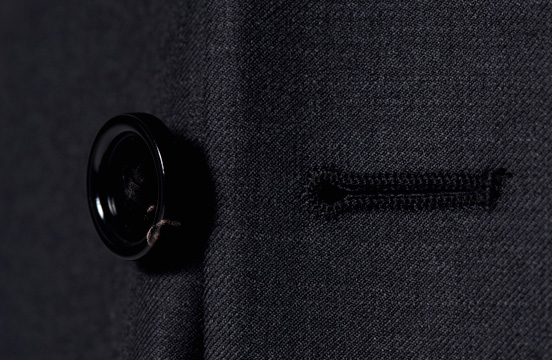 A close up of an INDOCHINO button on a suit.