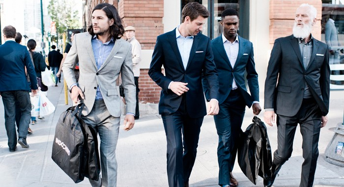 Four men dressed in INDOCHINO suits crossing the street.