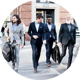 A group of men wearing INDOCHINO suits crossing the street.