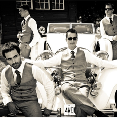 Grooms party wearing INDOCHINO suits lounging on antique car.