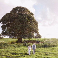 A couple in a lush green field about to be married.
