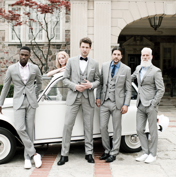 A wedding party posing in front of a car wearing INDOCHINO custom suits.