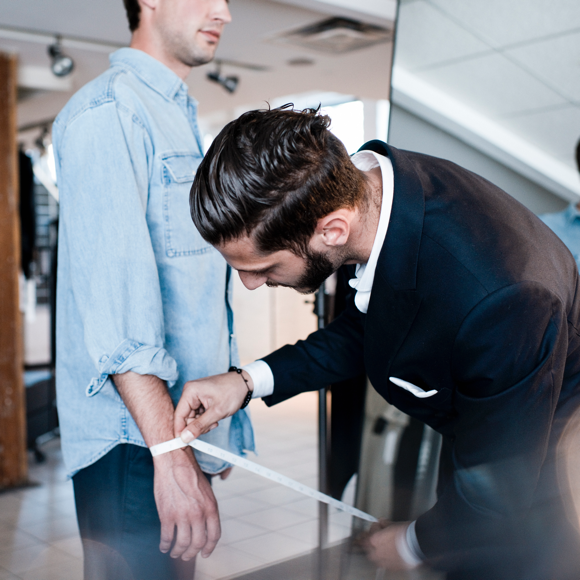 An INDOCHINO style guide measuring a customer.